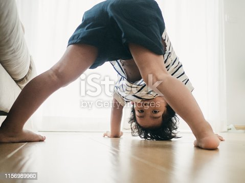 Asian baby boy playing in living room at home.
