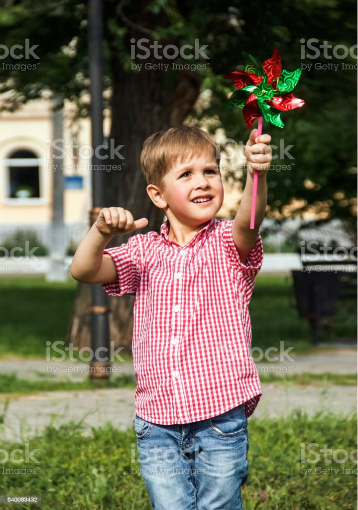 Happy little boy playing in the park,   summer day stock photo