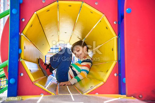 Happy little boy playing in tube or tunnel at the modern playground. Summer holidays. Happy and healthy childhood.