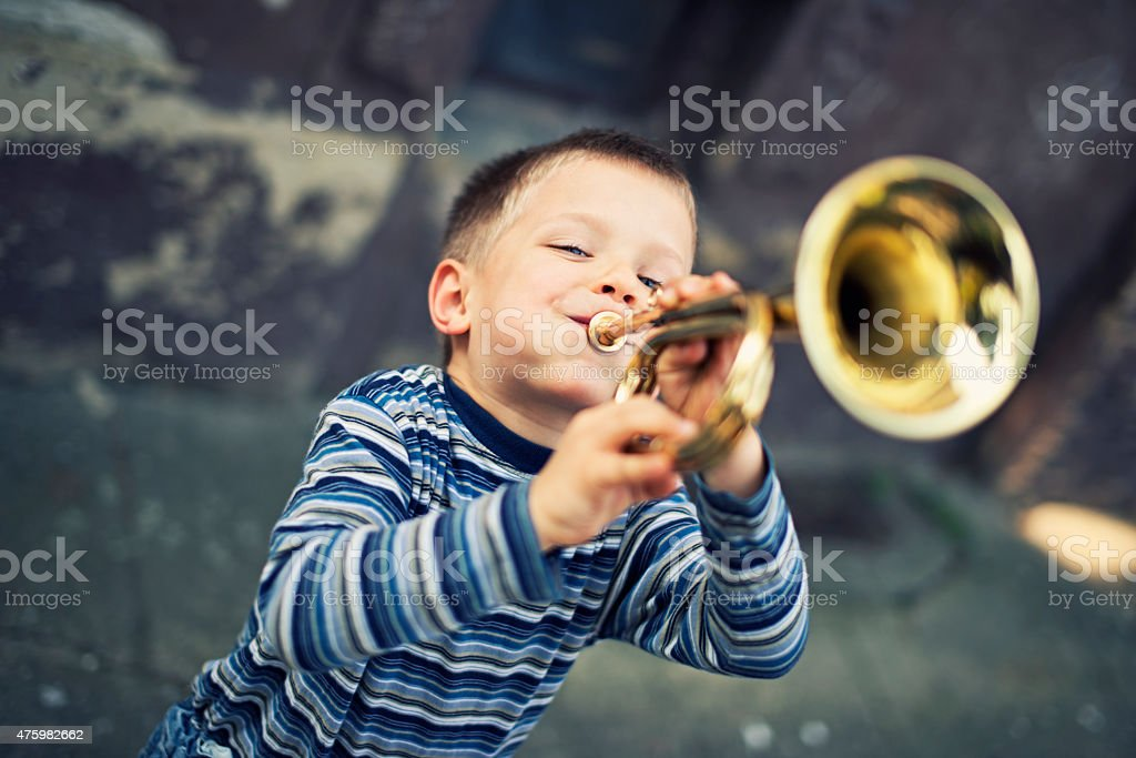 Happy little boy playing trumpet stock photo