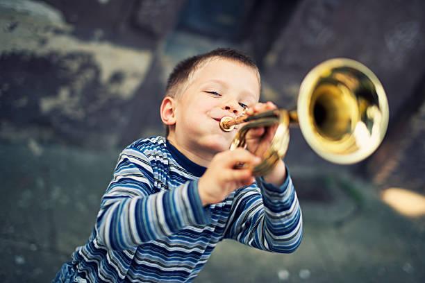 Glücklich kleiner Junge spielt Trompete – Foto