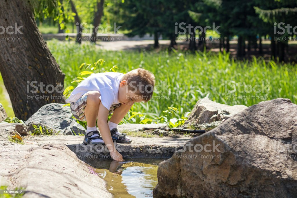 Happy little boy playing with water at the pond in the city park on a summer sunny day. Close up. Beautiful summer background with copy space stock photo