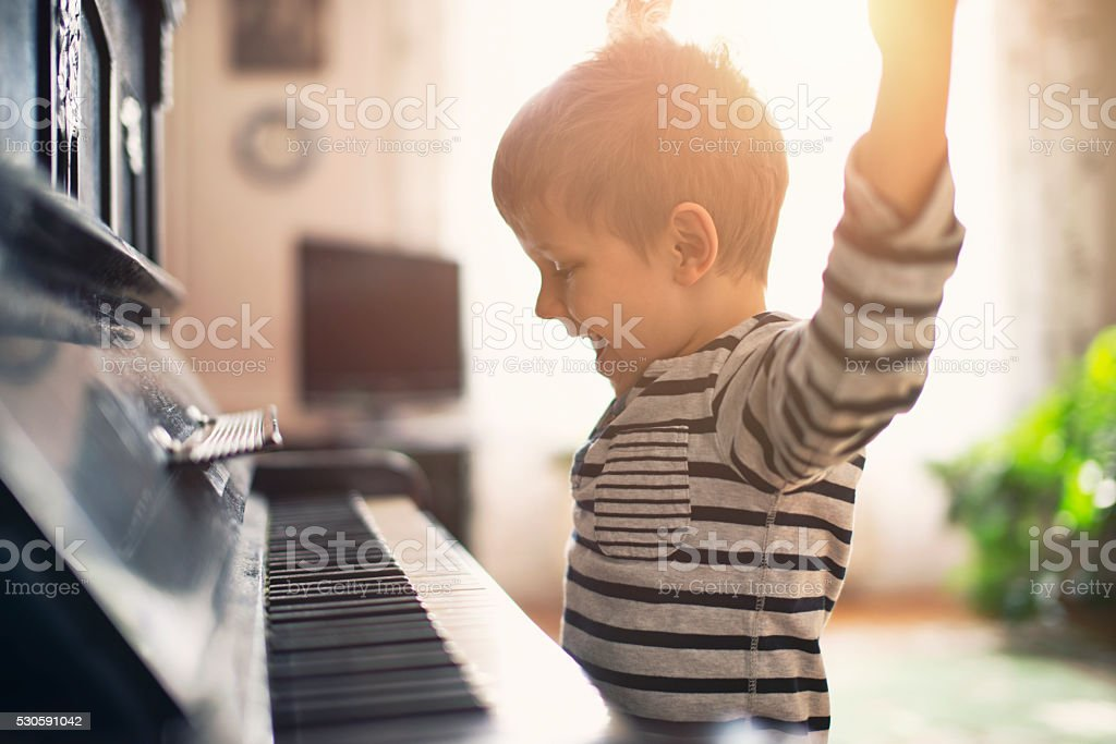 Happy little boy practicing piano stock photo