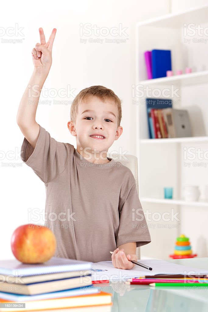 Happy little boy raising his hand to answer a question royalty-free stock photo