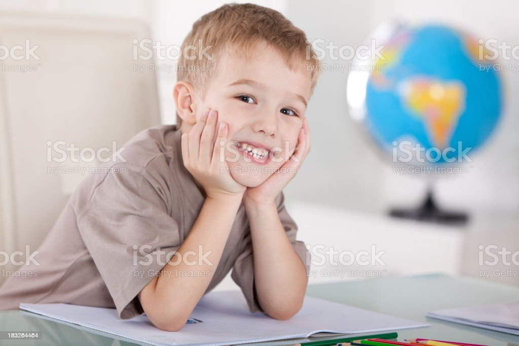 Happy little boy relaxing in the classroom stock photo