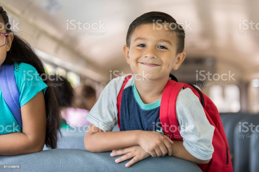 Happy little boy riding a school bus stock photo