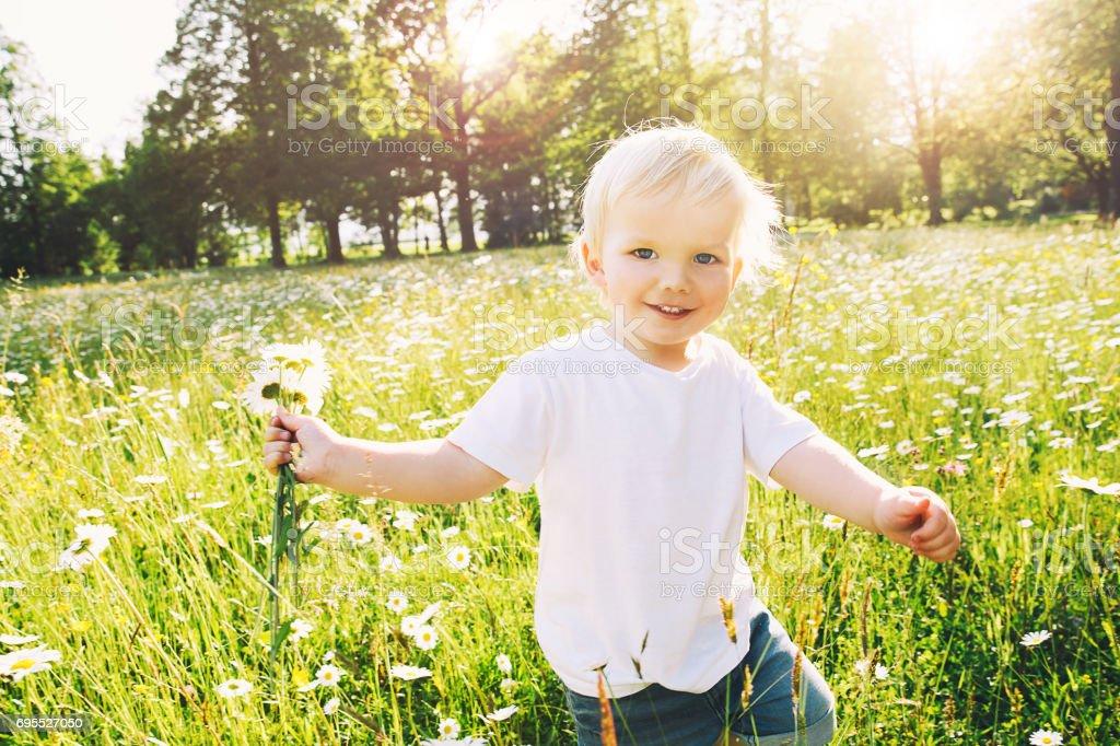 Glückliche kleine Junge läuft auf Wiese Blumen mit Bouquet von wilden Gänseblümchen. – Foto