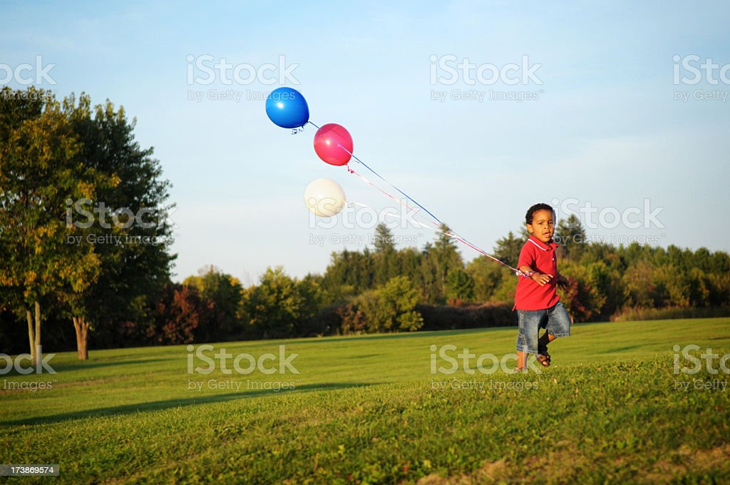 Happy Little Boy Running with Balloons Outside royalty-free stock photo