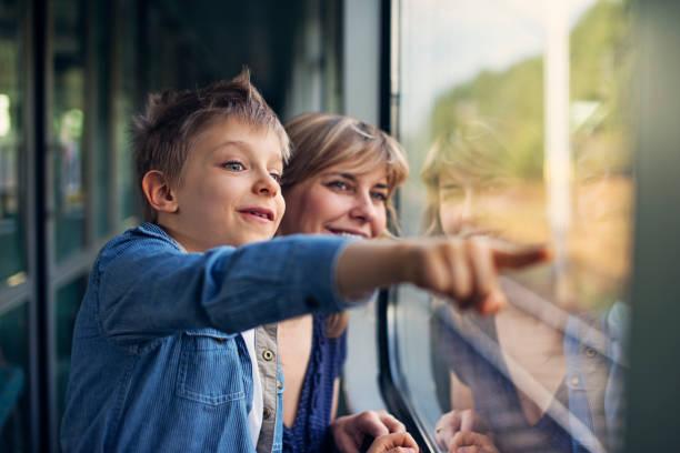 glückliche kleine junge reisen auf zug mit mutter - bahn reisen stock-fotos und bilder