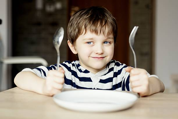 Happy little boy waiting for dinner. Happy little boy waiting for dinner. Holding a spoon and fork in the hand hungry child stock pictures, royalty-free photos & images