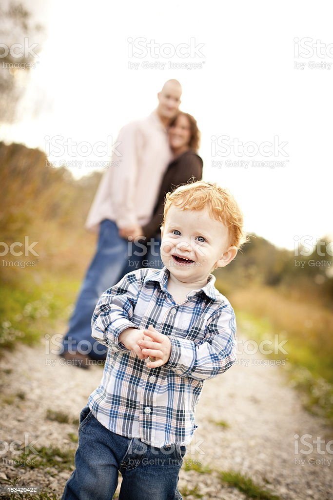 Happy Little Boy Walking Outside with Dad and Mom royalty-free stock photo