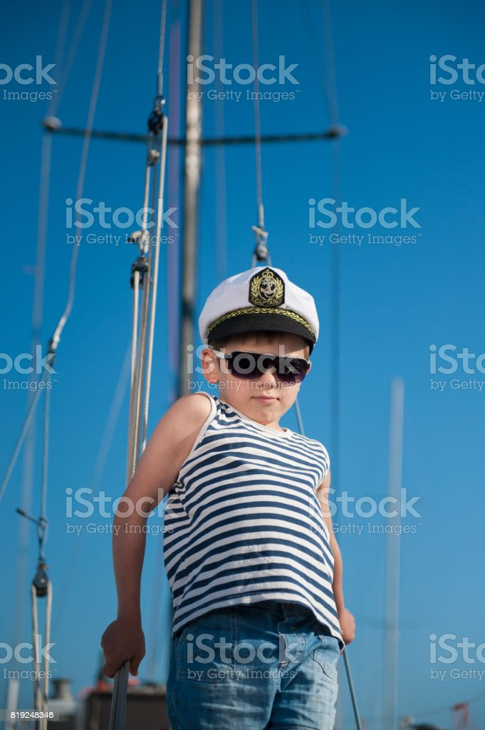 happy little boy wearing captain hat and sailor striped shirt aboard recreational boat stock photo