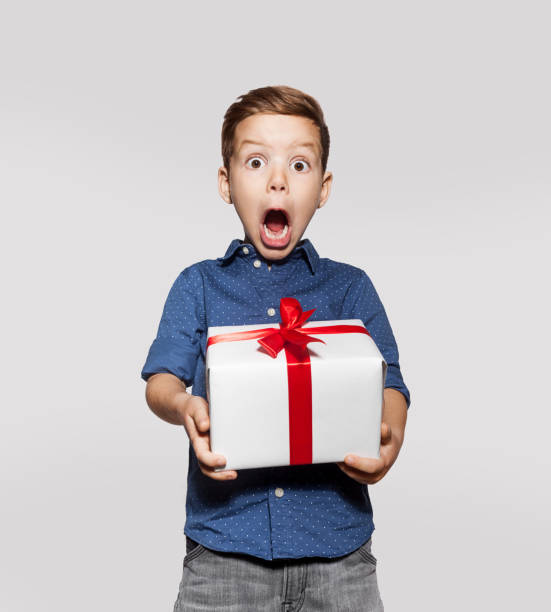 Happy little boy with a gift, white box with red ribbon stock photo