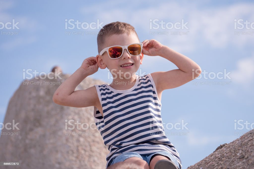 Happy little boy with fashionable sunglasses and sailor stripes shirt royalty-free stock photo