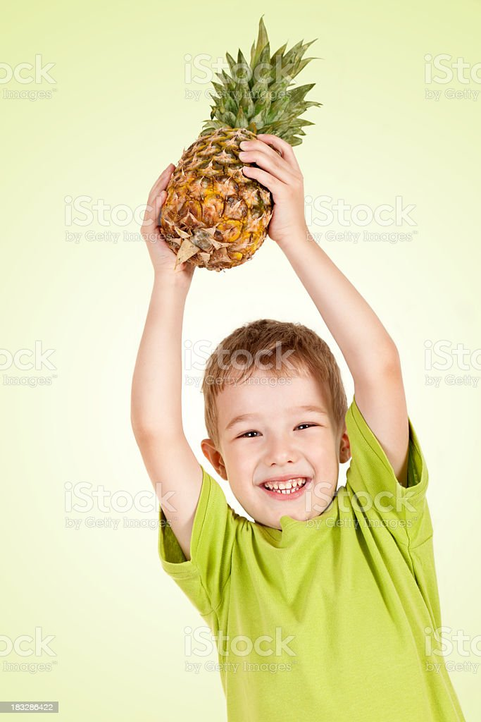 a8265e0b227e6 Happy little boy with hands raised holding pineapple - Stock image .