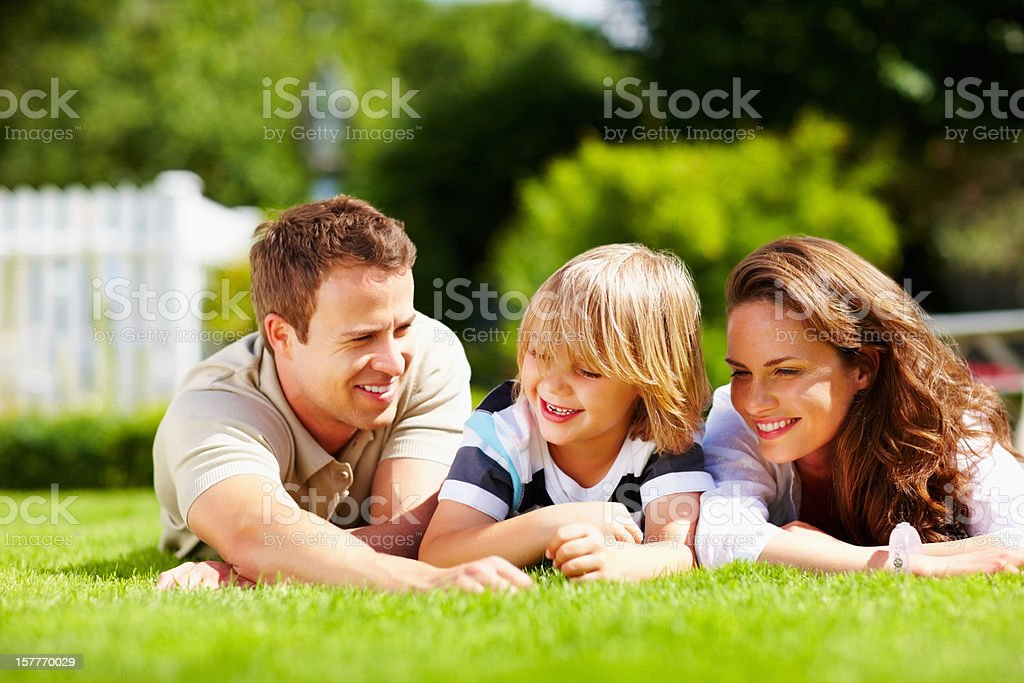 Happy little boy with his parents lying on grass royalty-free stock photo