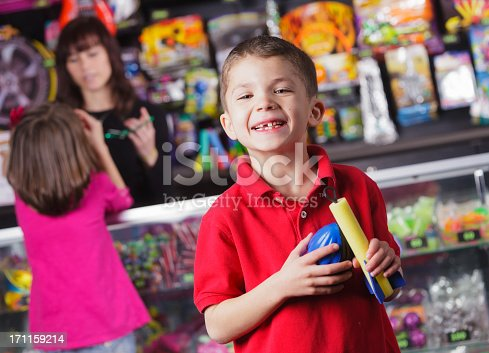 A happy young boy showing prizes he won at a game arcade.