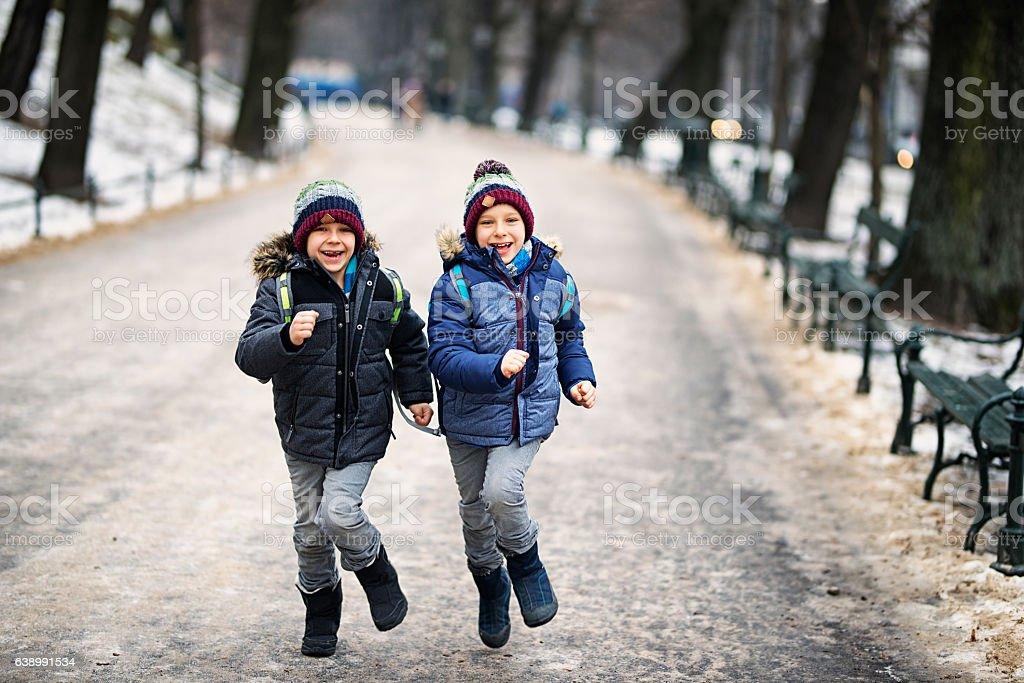 Happy little boys running from school in winter stock photo