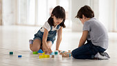 istock Happy little brother and sister playing with wooden multicolored bricks. 1197547439