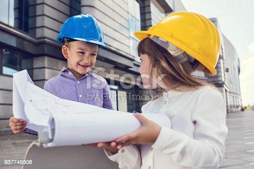 643843490istockphoto Happy little building contractors talking about blueprints outdoors. 637745508