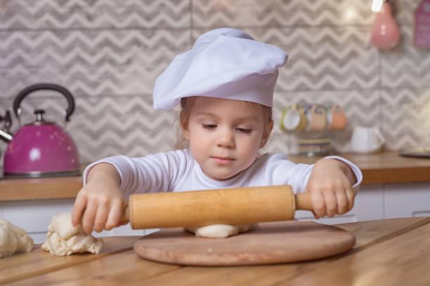 Glücklicher kleiner Koch in Kochhut mit Nudelholz macht Brot – Foto