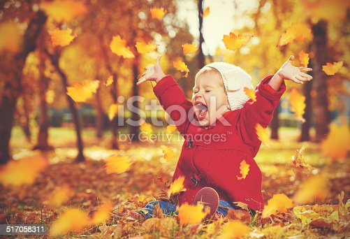 istock happy little child, baby girl laughing and playing in autumn 517058311