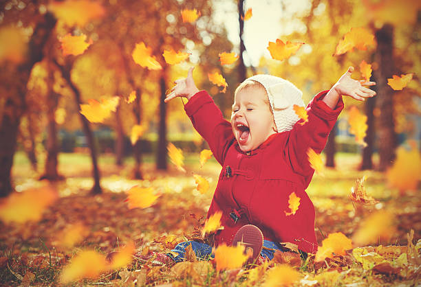 happy little child, baby girl laughing and playing in autumn - september stock photos and pictures