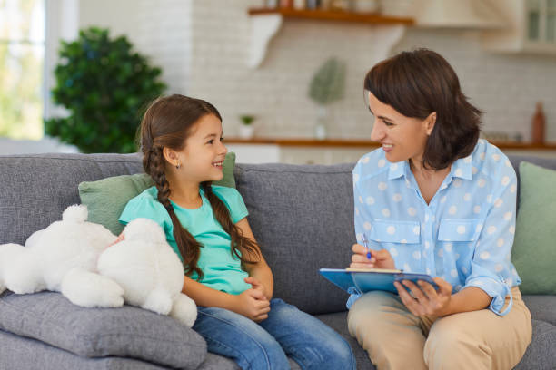 Happy little child communicating with psychologist sitting on sofa during therapy session at home stock photo
