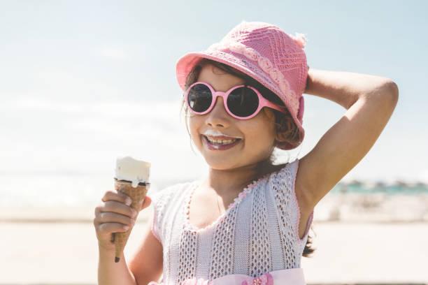 Glückliche Mädchen Kind genießen, Essen ein Eis am Strand im Sommer – Foto