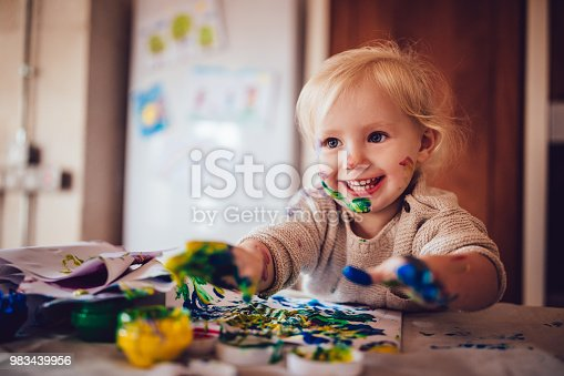 Cheerful little girl with dirty face and hands having fun painting with watercolor finger paints