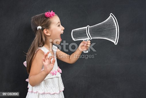istock Happy Little Child Schoolgirl Makes Announcement Call for Back To School 991060890