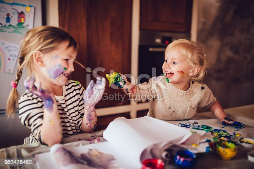 983418152 istock photo Happy little children having fun finger painting at home 983478482