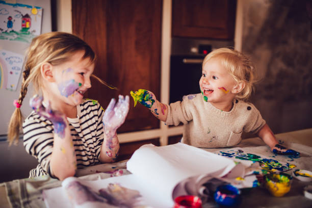 Happy little children having fun finger painting at home stock photo