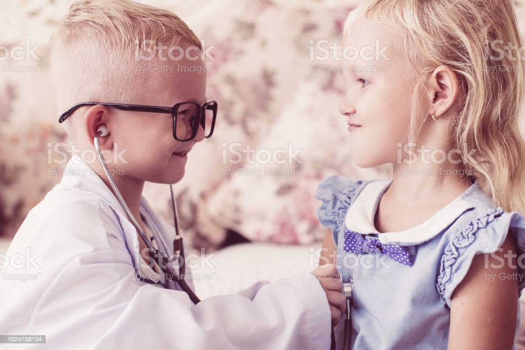 Happy little children playing doctor and patient stock photo