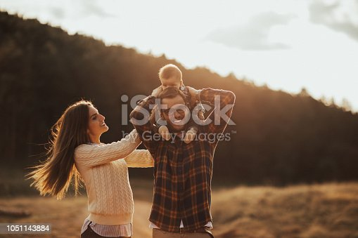 istock Happy little family enjoying autumn day in forest 1051143884