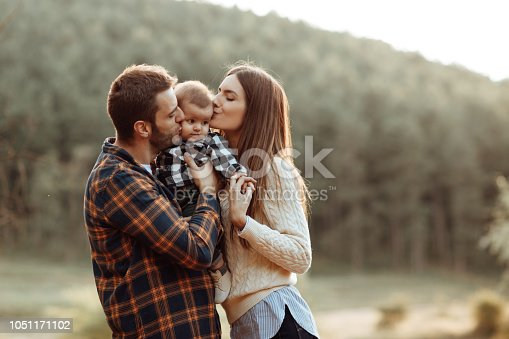 istock Happy little family enjoying autumn day in forest 1051171102