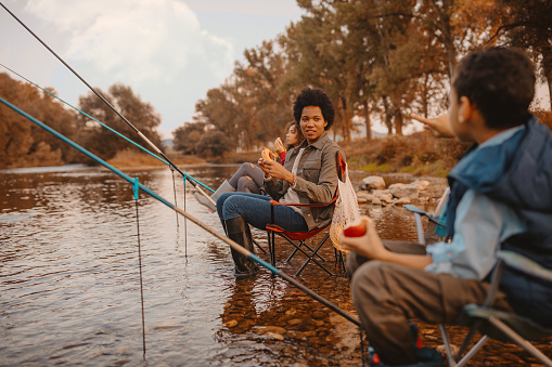 Happy little family enjoying snack while fishing. Sitting in the river on fishing chairs with fishing rods in water