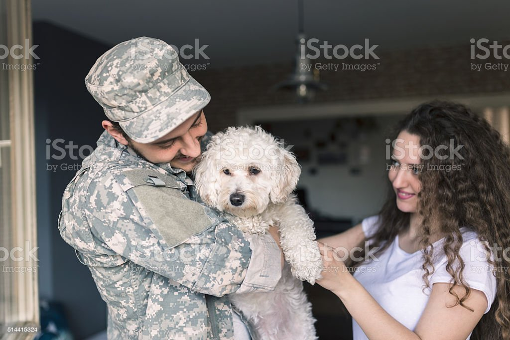 Happy little family. Soldier with his wife and puppy stock photo