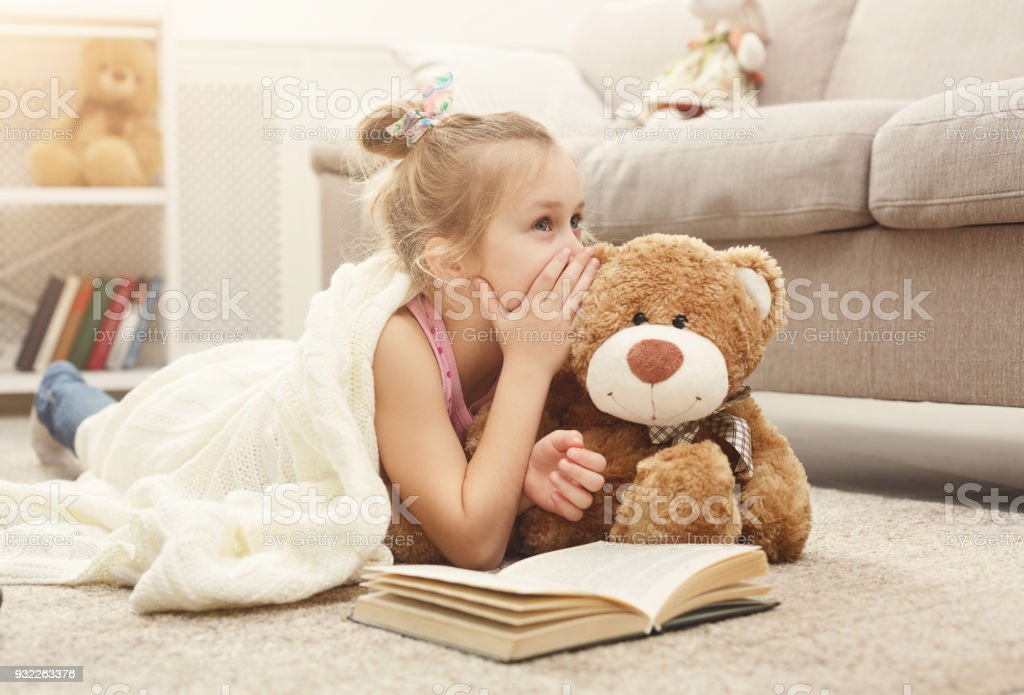 Happy little female child and her teddy bear reading book on the floor at home stock photo
