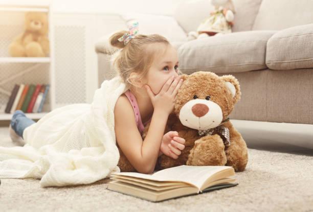 glückliche kleine mädchen und ihr teddy bär buch auf dem boden zu hause - teddybär stock-fotos und bilder