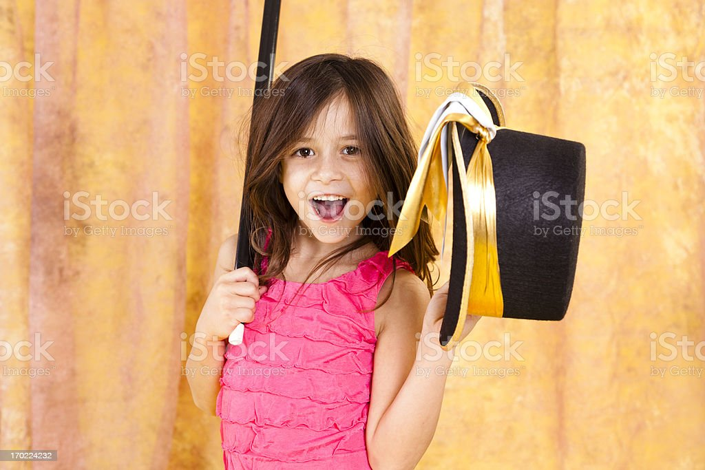 Happy little girl, 7-8, laughing dancing with top hat cane. stock photo