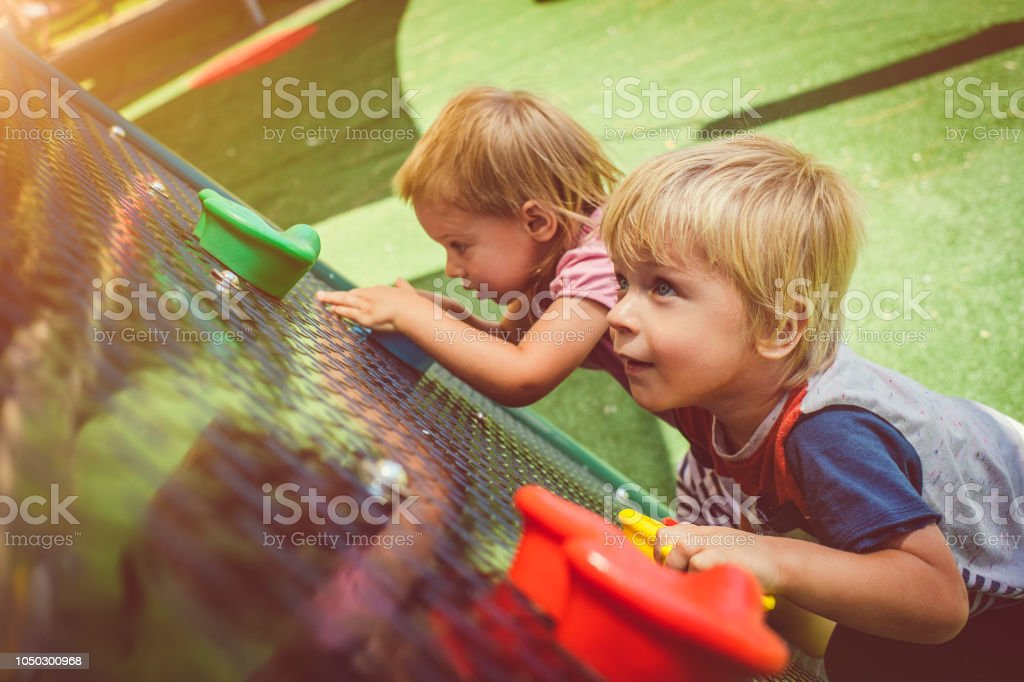 Happy little girl and boy climbing in playground stock photo