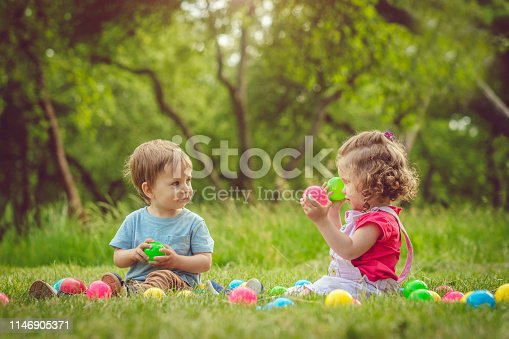 915609494istockphoto Happy little girl and boy playing in summer park 1146905371