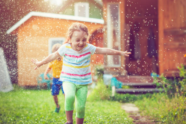 happy little girl and boy playing with garden sprinkler - water day stock photos and pictures