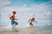happy little girl and boy run and play with water at beach vacation