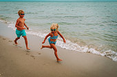 happy little girl and boy running at beach vacation