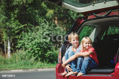 915609494istockphoto happy little girl and boy travel by car 998709914