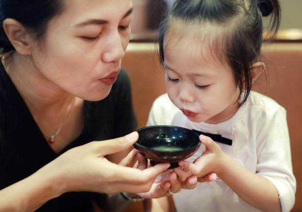 Happy little girl and mother blowing hot miso soup at japanese restaurant. stock photo