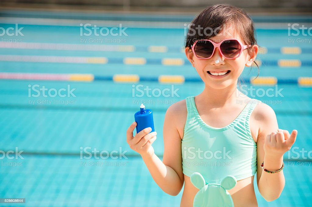 happy little girl applying sunscreen lotion on nose stock photo