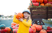 Happy little girl at the autumn pumpkin patch background. Having fun. Toned in retro style